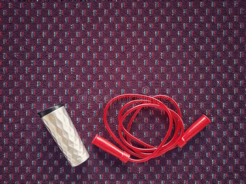 Water bottle and jumping red rope on a carpet floor at fitness g royalty free stock image