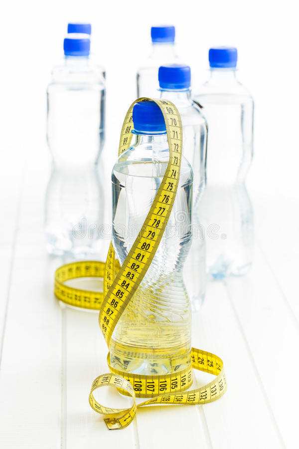 Water bottle and measuring tape. On white table stock photography