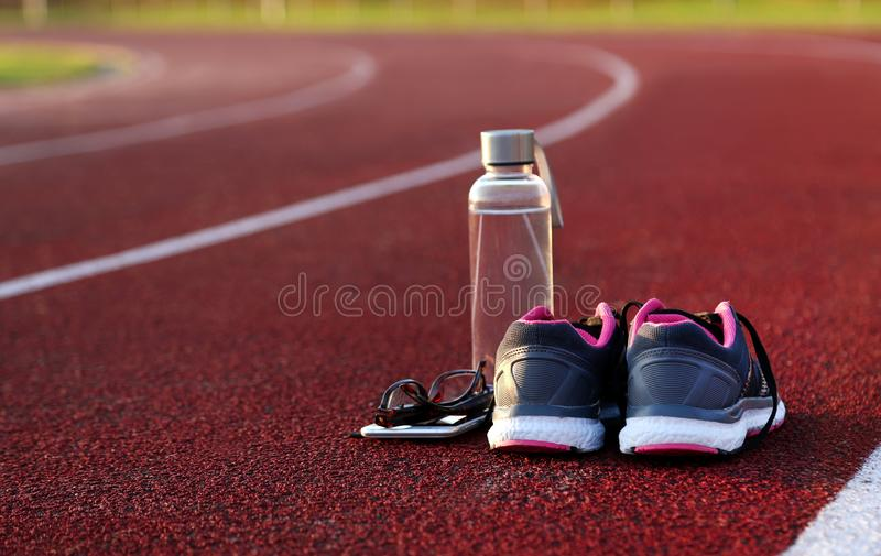 Water bottle and shoes on athletic track. At afternoon royalty free stock image