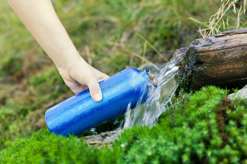 Water bottle and stream on hike stock image