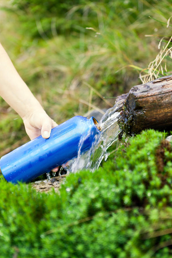 Water bottle and stream on hike royalty free stock photo
