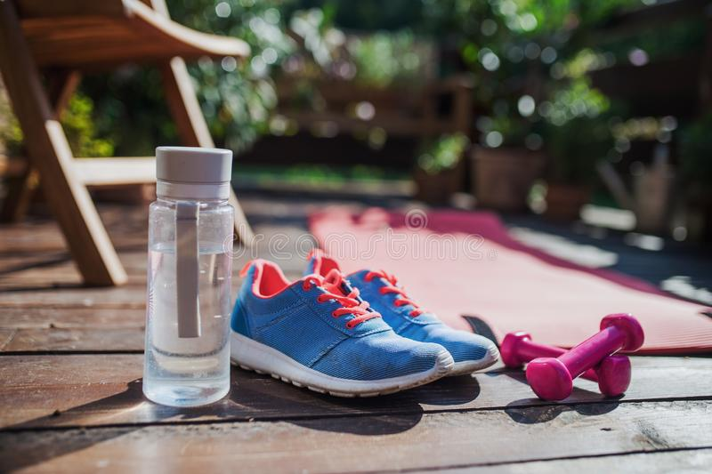Water bottle, trainers and dumbbells outdoors on a terrace in summer. stock photo