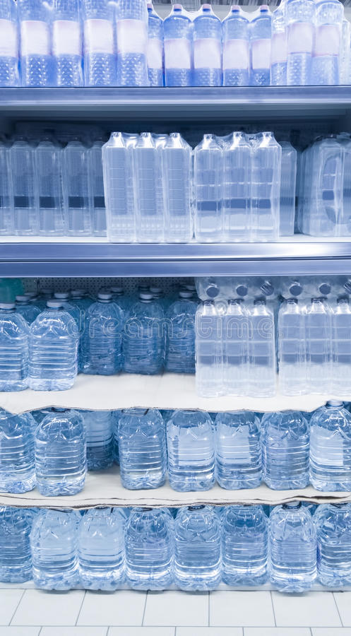 Water bottles on shelf. Stack of water bottles in shop royalty free stock images