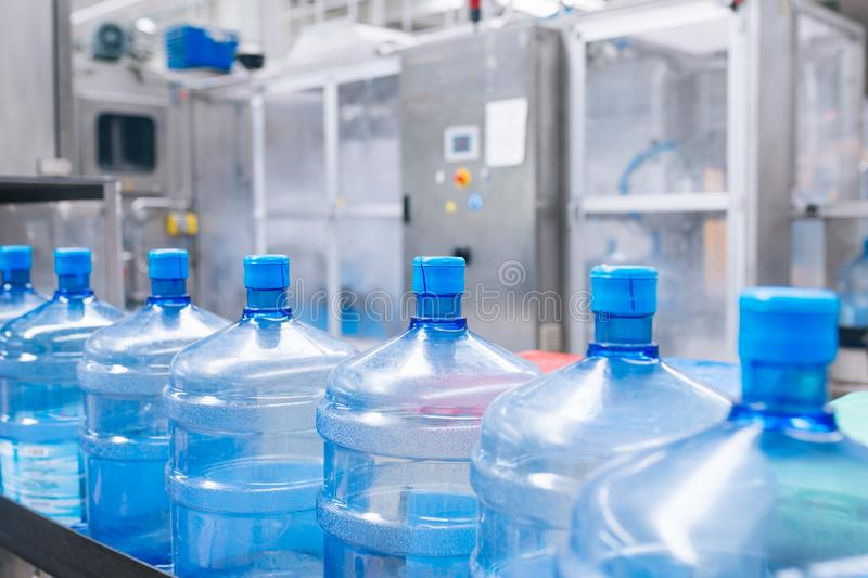 Water bottling factory. Bottling plant - Water bottling line for processing and bottling pure mineral carbonated water into bottles royalty free stock photos