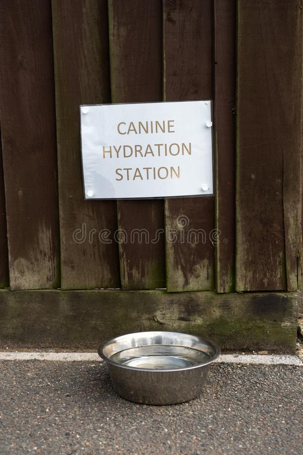 A water bowl for dogs and a sign canine hydration station.  royalty free stock photography