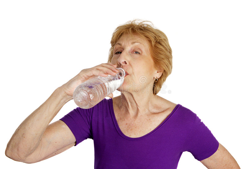 Water Break. A fit senior woman in her leotard taking a water break from exercising. Isolated on white stock images