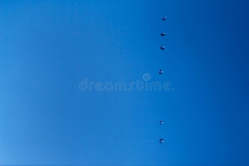 Water bubbles in the blue sky. Water drops on blue background. Aqua, rain, weather, clear. Life, freedom, ease stock image
