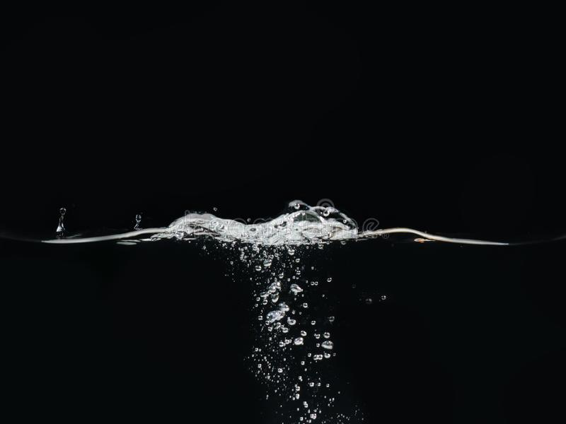 Water bubbles and rippling water surface isolated on black background, close up view. Liquid splashing. Abstract. Background for overlays design, screen royalty free stock photos