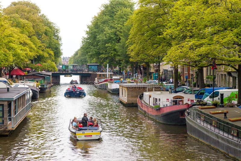 Water canal in Amsterdam with moored and sailing boats royalty free stock photography