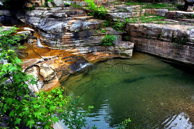 Cascade in the Ozarks. Water cascades from a Ozark Mountain spring. Calm and peaceful pool of clear water sits below small cascade stock images