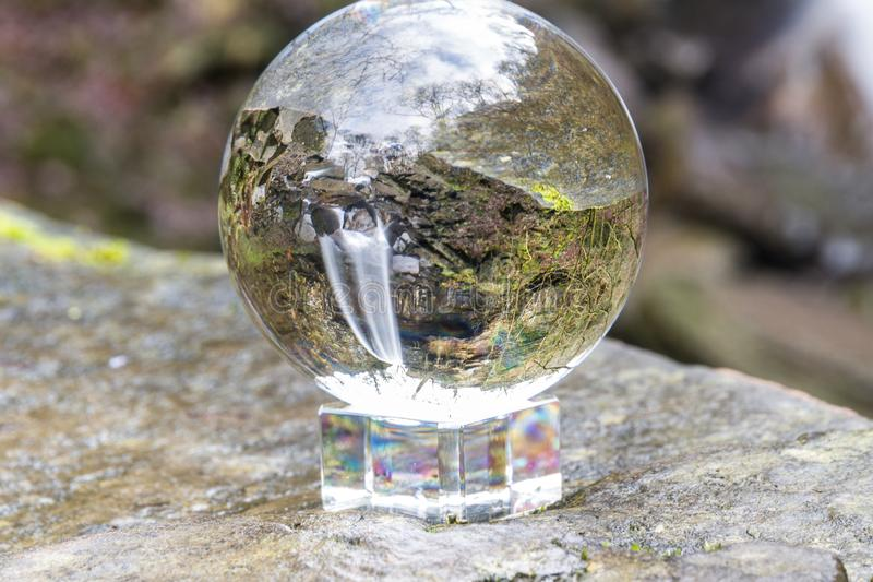 Water cascading down beautiful waterfall, Melincourt, through crystal ball. Crystal ball view of Melincourt Water Fall in full February flow stock images