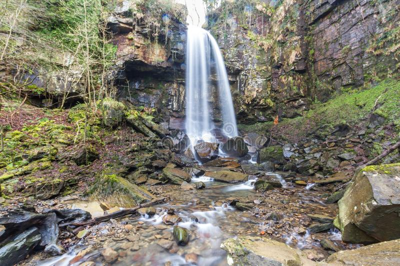 Water cascading down beautiful waterfall, Melincourt. Melincourt Water Fall in full February flow stock photography