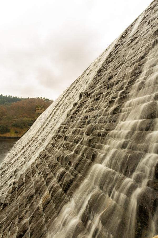 Water cascading down stone dam, Ladybower reservoir. royalty free stock photography