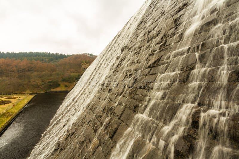 Water cascading down stone dam, Ladybower reservoir. stock photo