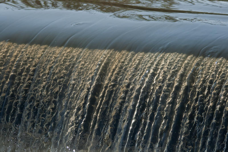 WATER CASCADING DOWN A WEIR. Small waterfall cascading down a weir royalty free stock photography