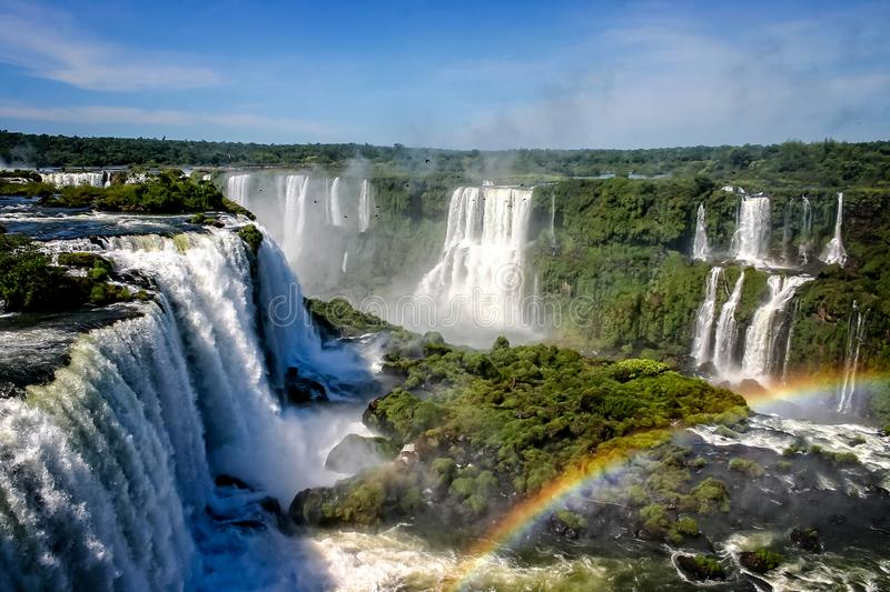 Water cascading over the Iguacu falls with rainbow in foreground royalty free stock photo