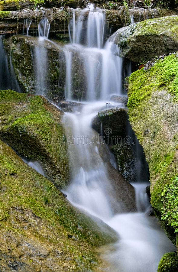 Water Cascading Over Rocks. A cascade of water flows down and around moss covered rocks stock photos