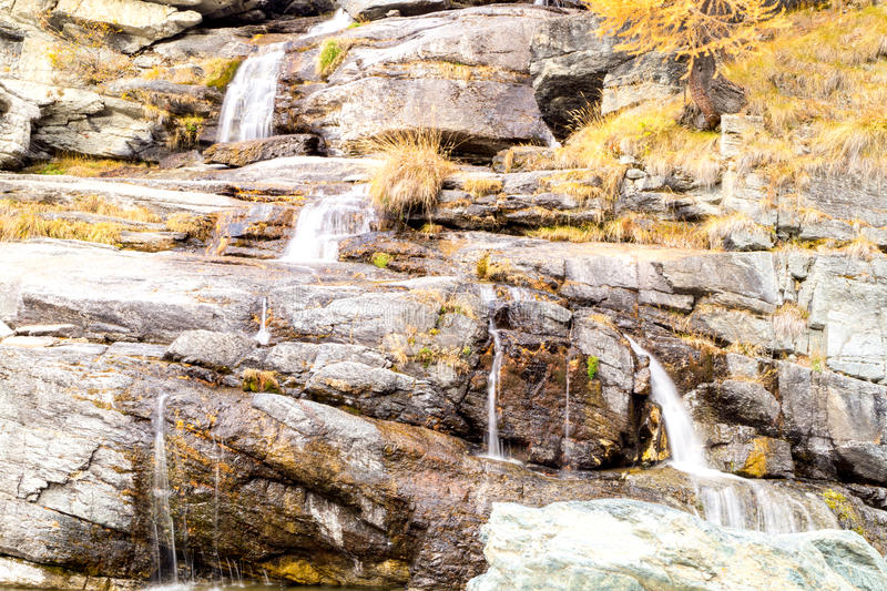 Water cascading over rocks, waterfall and autumn colors in the mountains, yellow and red trees stock image