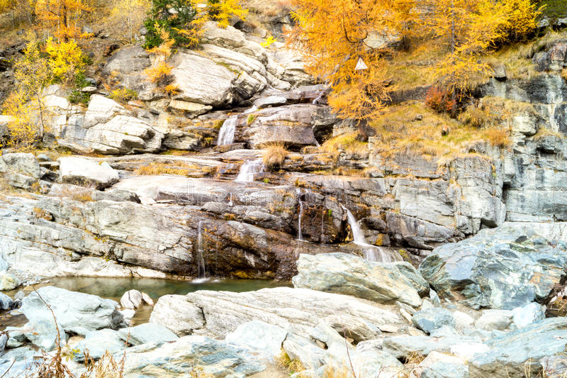Water cascading over rocks, waterfall and autumn colors in the mountains, yellow and red trees royalty free stock images