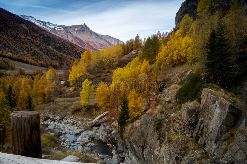 Water cascading over rocks, waterfall and autumn colors in the mountains, yellow and red trees stock photos