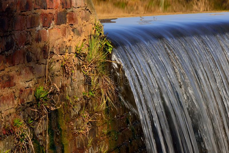 Water Cascading Over Weir. Water falling over weir in river on farm near Skeerpoort South Africa royalty free stock photography