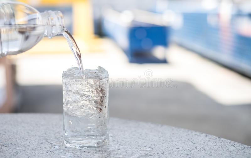 The water is in a clear bottle with a glass of ice. Water with Ice suitable for summer season stock images