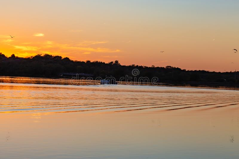 Water craft or boat on the lake at dusk with ripples on the lake. Water craft or boat on the lake. Fall colors at dusk with ripples on the lake. Colorful skyline royalty free stock images
