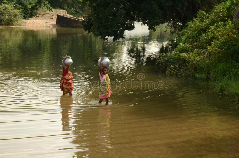 Water Crisis In India. Women carrying drinking water from far more distance in Purulia.In India water crisis is a burning issue for society. Particularly in royalty free stock photo