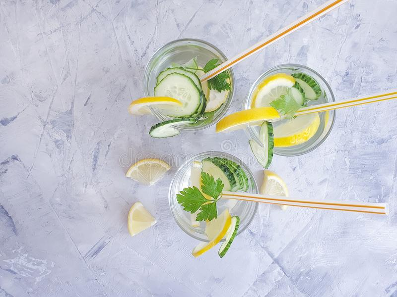 Water cucumber, lemon parsley cocktail flavored summer on a gray concrete background. Water cucumber, lemon parsley a gray concrete background summer cocktail stock image