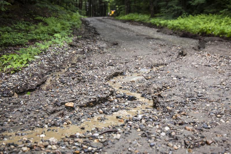 Water Damage of Dirt Road. A washed out and damaged rural dirt road from rain and weather being repaired by road equipment in background stock image