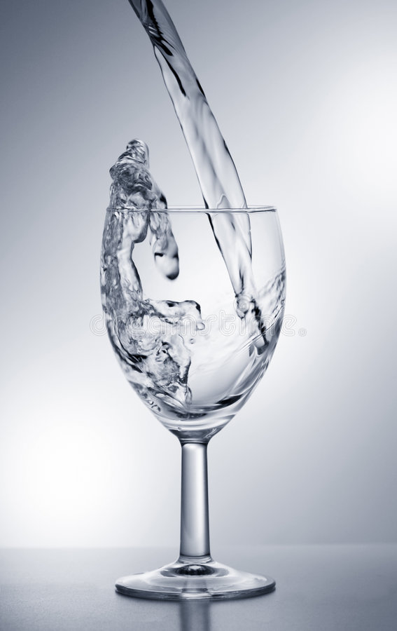 Water dat in glas valt stock foto's