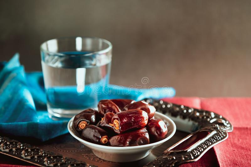 Water and dates on metal tray and blue and red napkins. Traditional Ramadan Iftar food. royalty free stock photos