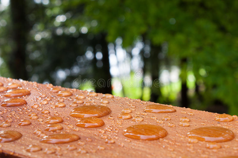 Water on the deck rail. Water beads on the freshly treated deck rail, after a summer rain at the summer cottage stock images