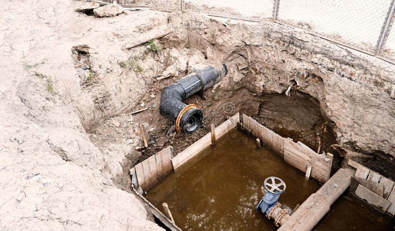 Water Delivering PVC Plastic Pipes in Ground Hole during Plumbing. Vintage color look stock photography