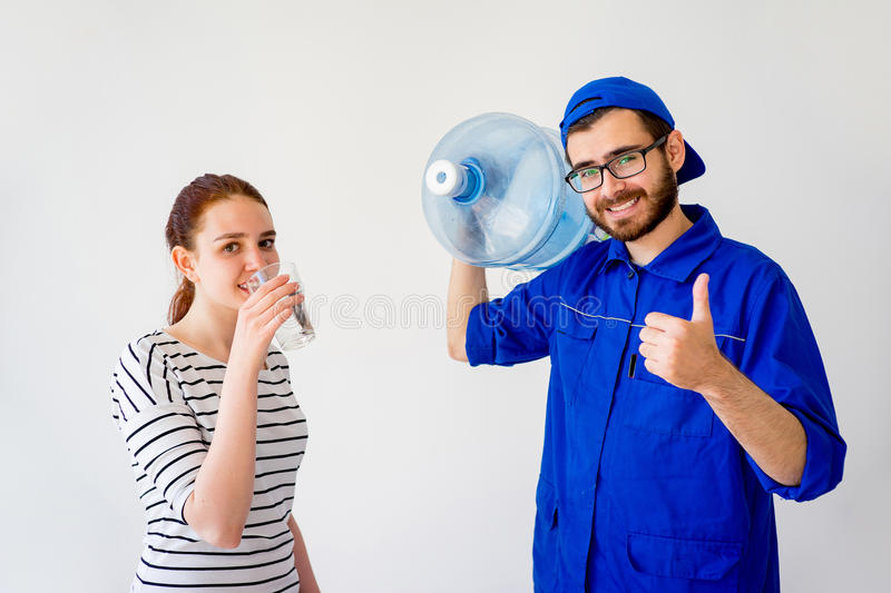 Water delivery into office. Water delivery into an office: a guy in blue shirt brings a canister stock photography