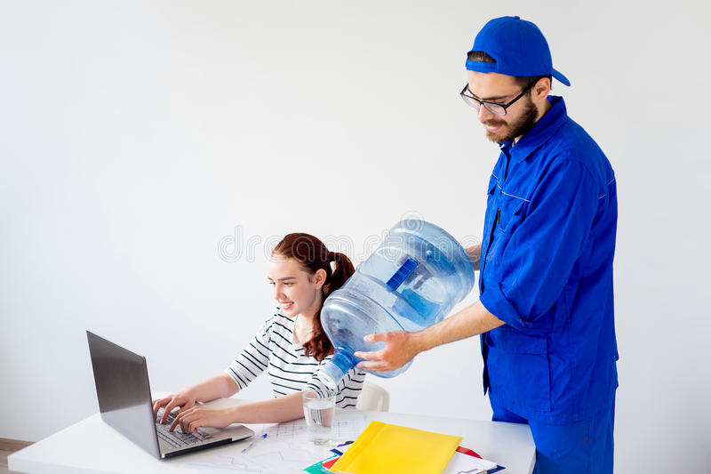 Water delivery into office. Water delivery into an office: a guy in blue shirt brings a canister stock photo