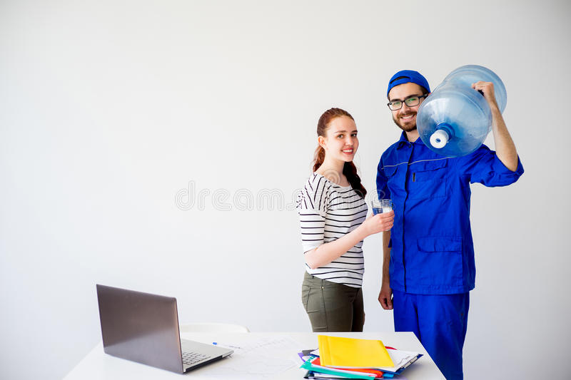 Water delivery into office. Water delivery into an office: a guy in blue shirt brings a canister royalty free stock image