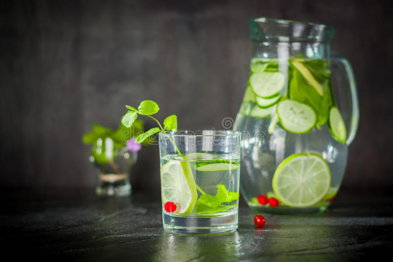 Water detox in a glass jar and a glass. Fresh green mint and berries. A refreshing and healthy drink. royalty free stock photos