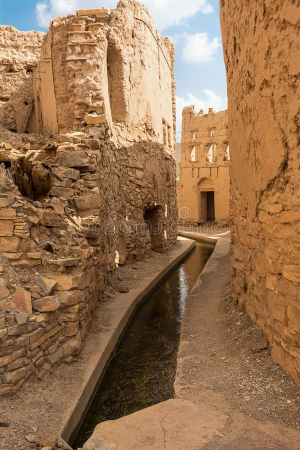 Water die Aflaj in de stegen tussen de semi-verlaten modderhuizen channeling van Birkat Al Mouz stock afbeeldingen