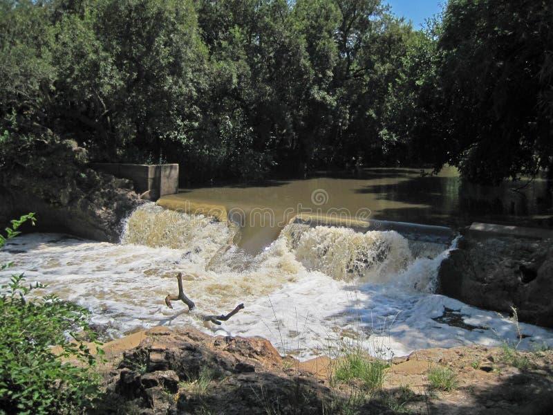 WATER DIE ONDERAAN EEN WATERKERING IN EEN RIVIER DRAPEREN royalty-vrije stock afbeeldingen