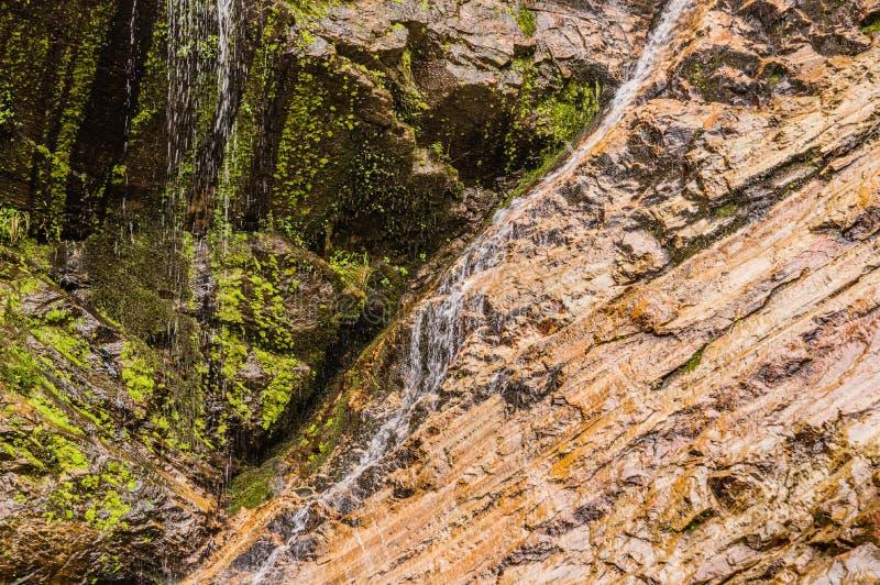 Water die onderaan rotsachtige richel stromen stock afbeelding