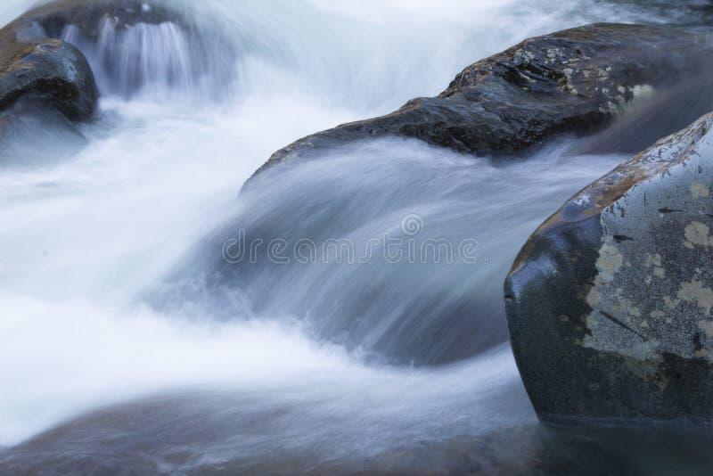 Water die over grote rotsen in een snel bewegende koude bergstroom meeslepen royalty-vrije stock fotografie