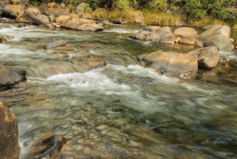 Water die over snel met rotsen en keien stromen royalty-vrije stock afbeelding