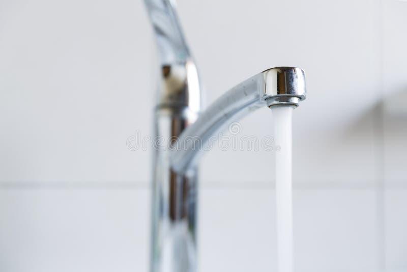 Water die van een kraan een badkamersgootsteen tegenkomen stock foto
