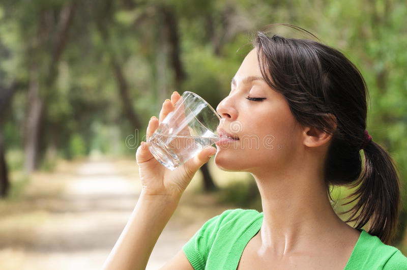 Water drinking in glass. Young woman drinking with water glass stock photos