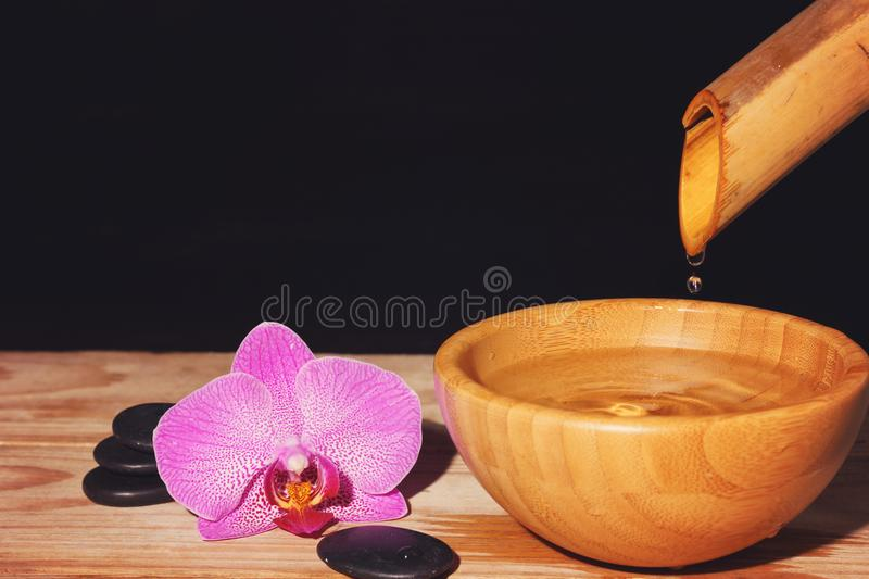 Water drips from the bamboo in a bowl on a wooden table, next to the spa treatment stones and orchid flower, copy space for your t stock photos