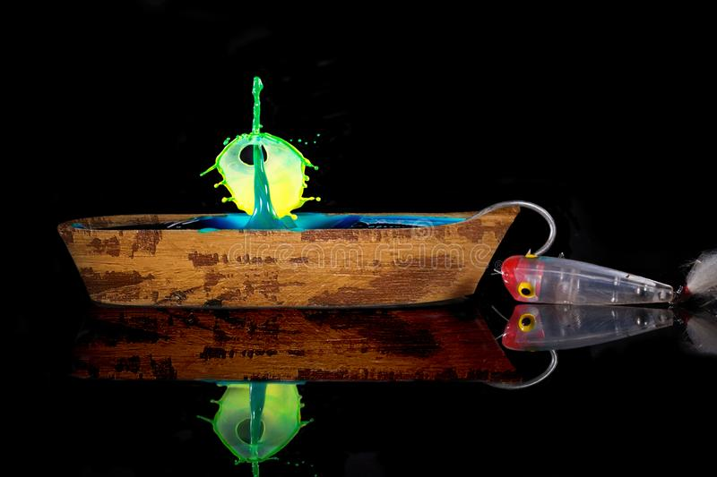 A Water Drop Collision Into A Miniature Wooden Boat. A Water drop breaks the surface and pierces another drop coming down. Both are dropped into a miniature royalty free stock photo