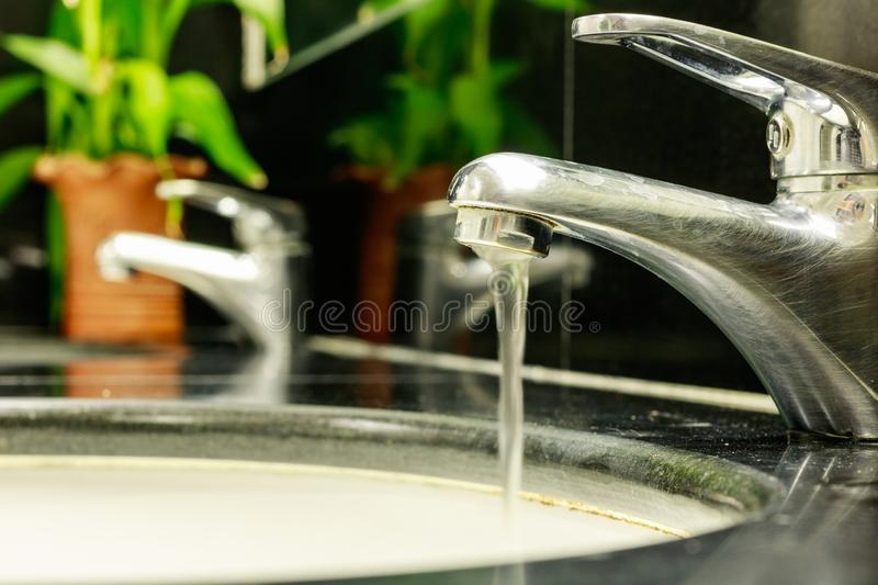 Water drop from dirty faucet in bathroom or toilet. Water saving stock photography