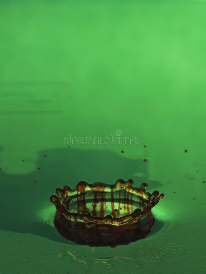 Water drop in green liquid