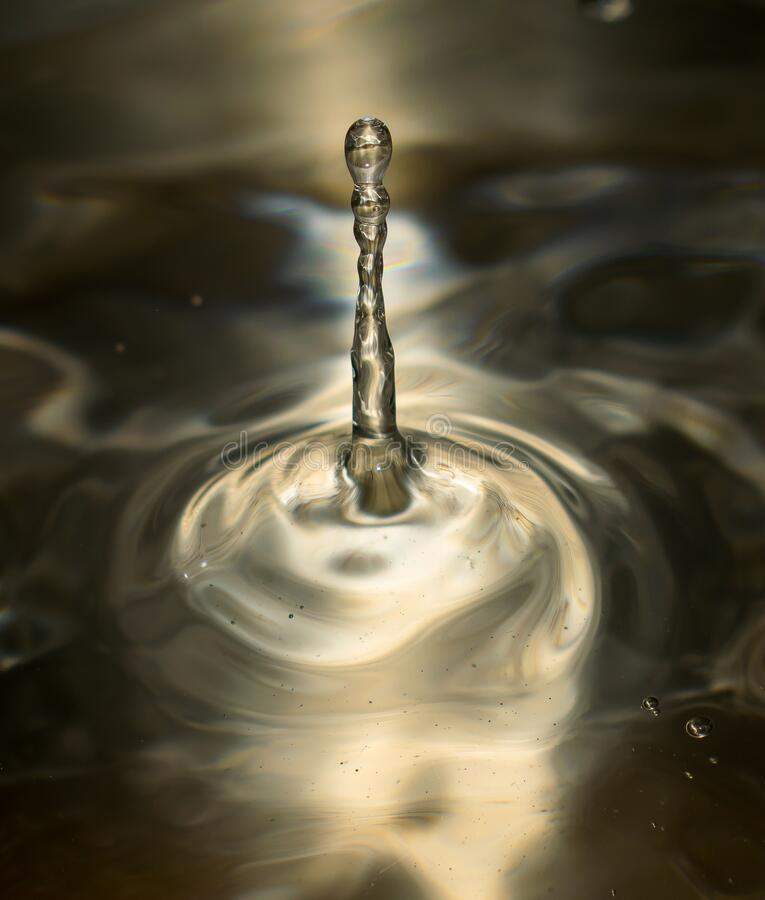 Water drop splash in a glass. The water droplet is shaped like a tower. Metallic color. Concept about water royalty free stock image